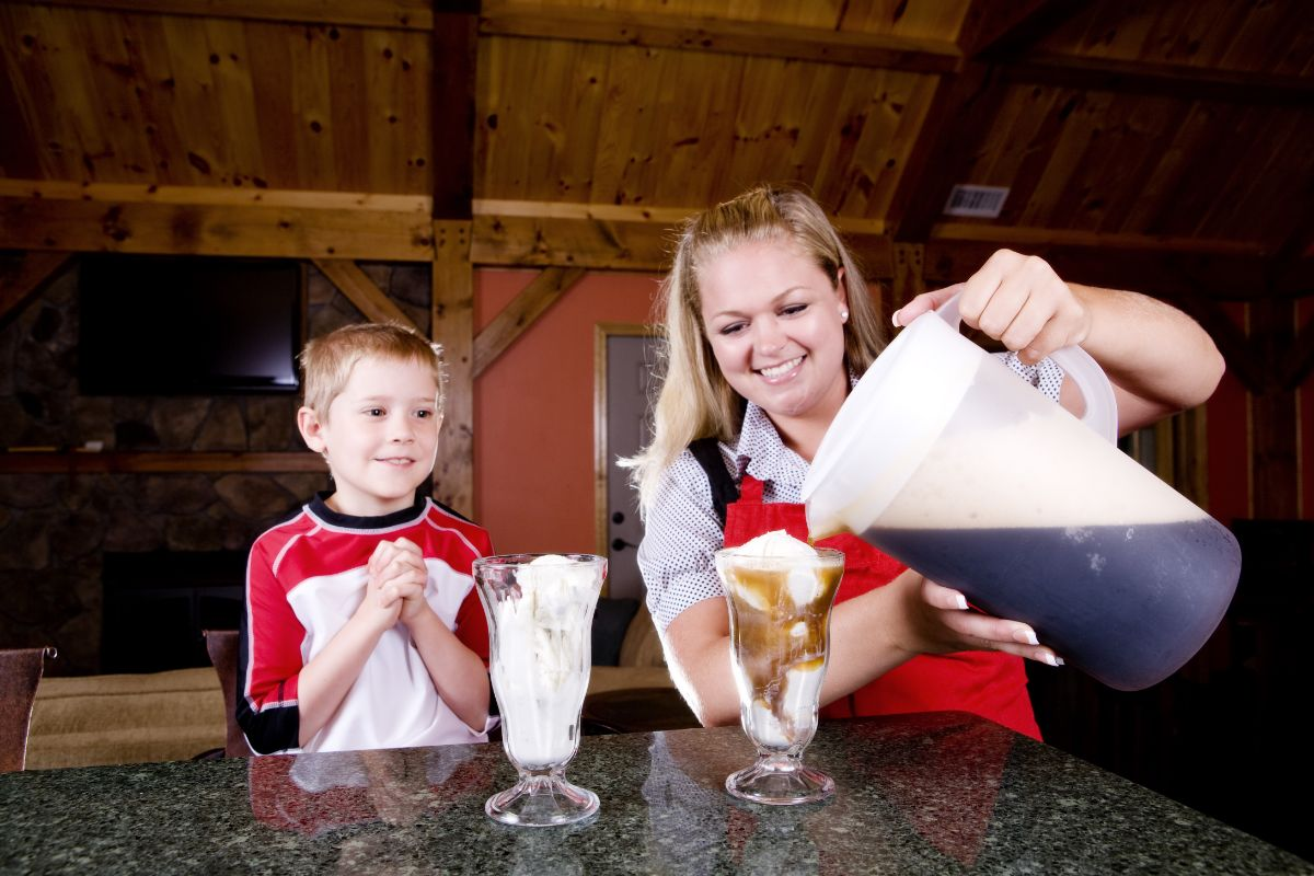 mom pouring rootbeer on glass with ice cream